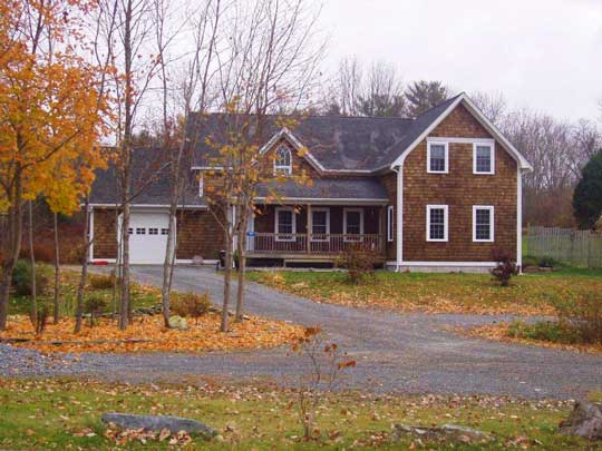Large two storey, new house, with wood shingle siding, neat white trim and attached garage