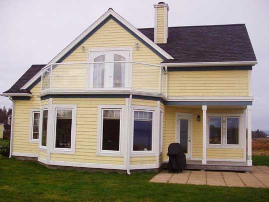 New home features second floor deck with glass railing to provide unobstructed view of the ocean