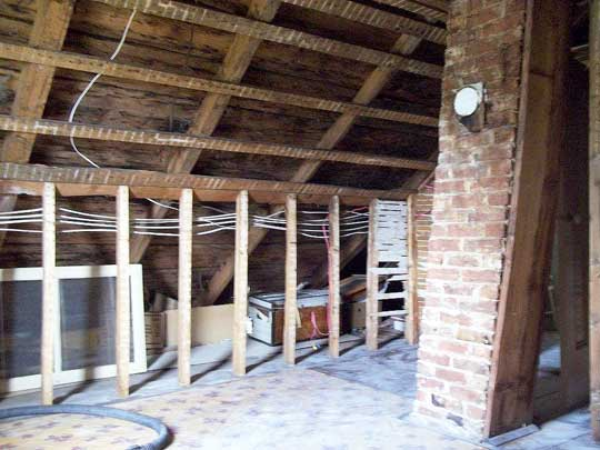 Interior view of attic space of Cape Cod home with new wiring; old plaster already removed