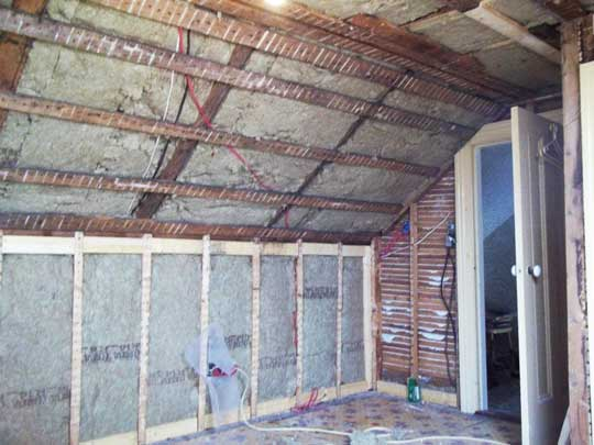Interior view of attic space of Cape Cod home with new insulation in knee wall and ceiling