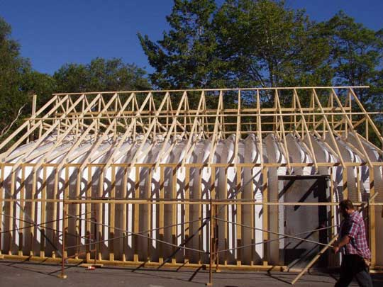 Side view of wall framing and roof trusses of renovation job to coverup existing Quonset hut