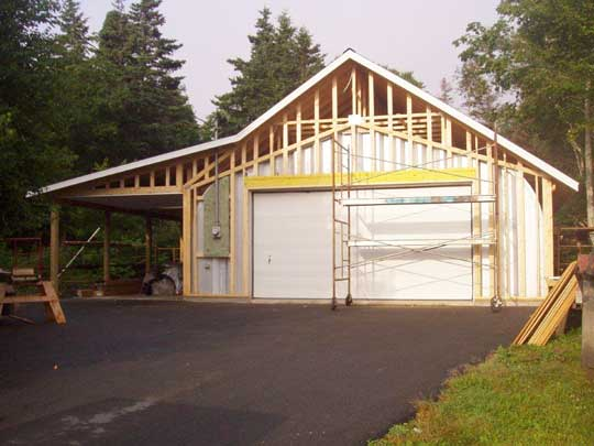 Gable end walls framed up, and roof installed over Quonset hut