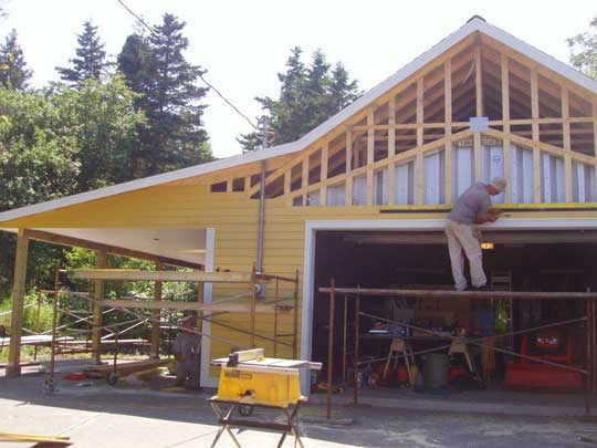 Yellow siding installed over framing around Quonset hut, and on car port addition on the side