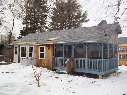 New roof over the bay window added to the heritage Caledonia split log siding cottage.