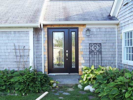 Elegant new entrance door with side light installed in existing home