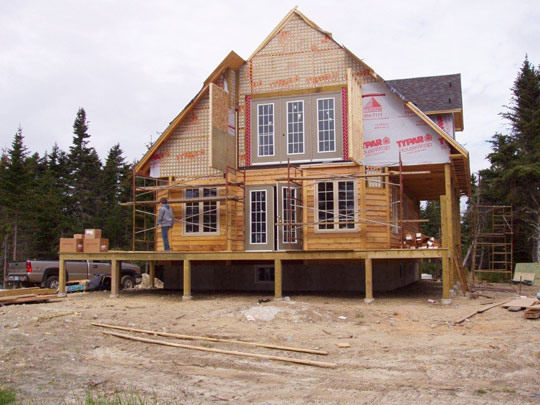 Wood siding partially installed, and roofing underway on new beachfront home.